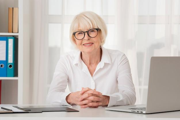 Donna anziana di smiley con gli occhiali che si siedono nel suo ufficio Foto Gratuite