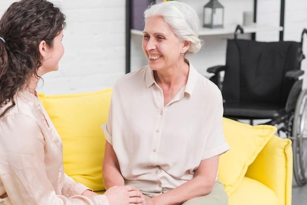 Donna anziana felice con sua figlia che si siede sul sofà a casa Foto Gratuite