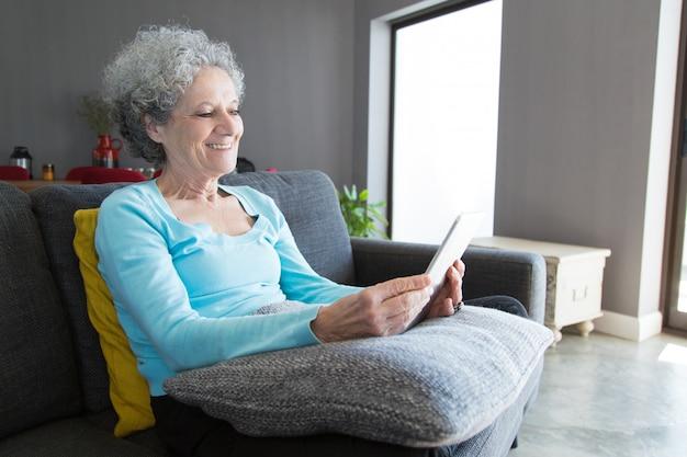 Donna anziana positiva felice che per mezzo della compressa Foto Gratuite