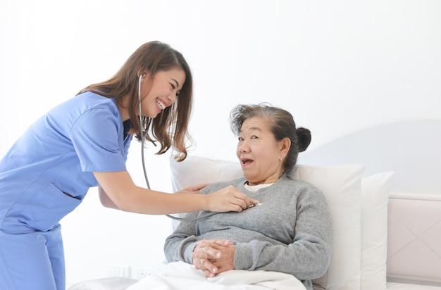 Donna anziana senior asiatica sul letto con medico e suo figlio in ospedale Foto Premium