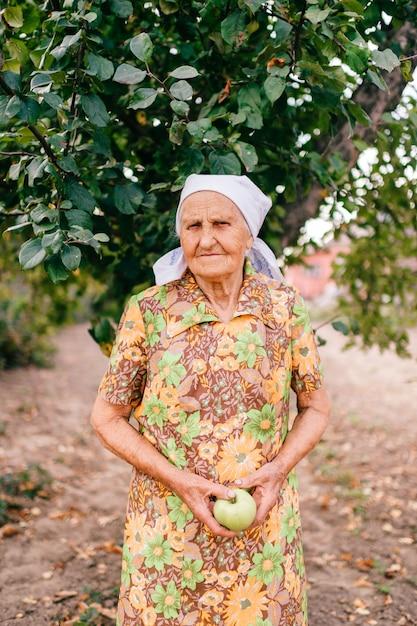Donna anziana sola con la mela verde in mani che stanno nel giardino davanti a di melo Foto Premium