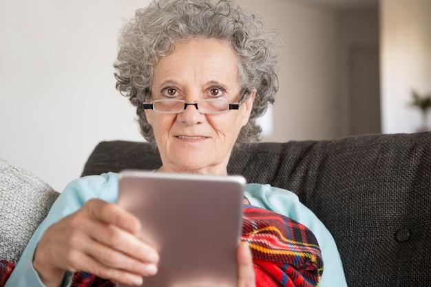 Donna anziana sorridente in vetri che legge le notizie di internet Foto Gratuite