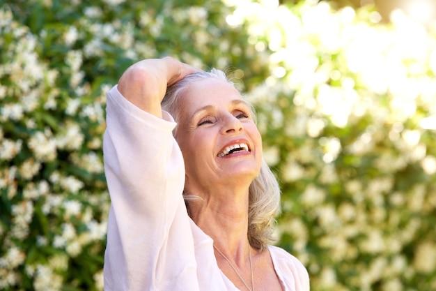 Donna anziana spensierata fuori con la mano nei capelli ...