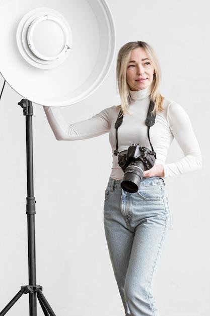 Donna appoggiata su una lampada da studio Foto Gratuite