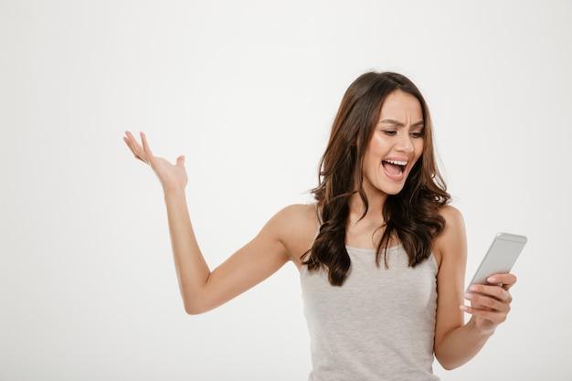 Donna arrabbiata del brunette che per mezzo dello smartphone e gridando sopra il gray Foto Gratuite
