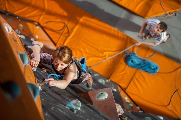 Donna arrampicata su roccia con carabine e corda su una parete di arrampicata indoor Foto Premium