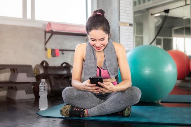 Donna asiatica astuta in telefono della tenuta degli abiti sportivi alla palestra di forma fisica. Foto Premium