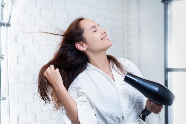 Donna asiatica che asciuga i suoi capelli dopo la doccia ...