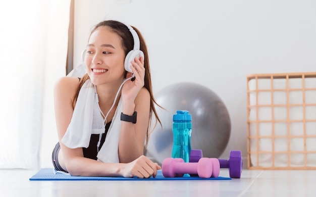 Donna asiatica che ascolta la musica con la cuffia dopo yoga del gioco ed esercizio a casa Foto Premium