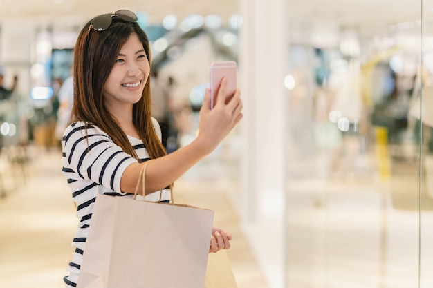 Donna asiatica che cammina e che utilizza il telefono cellulare intelligente per selfie con modello display mockup Foto Premium