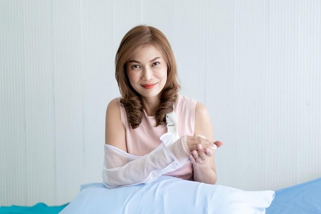 Donna asiatica che esamina il suo braccio che ha ferito dall'incidente. concetto di assistenza sanitaria e benessere negli adulti. Foto Premium