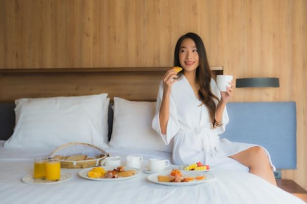 Donna asiatica che gode con la colazione sul letto Foto Gratuite