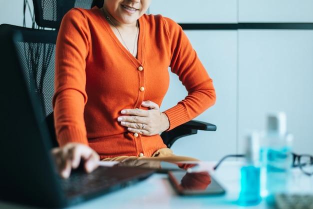 Donna asiatica che ha mal di stomaco doloroso durante il lavoro da casa Foto Premium