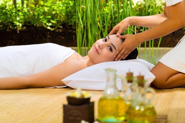 Donna asiatica che ha un massaggio nella regolazione tropicale Foto Premium