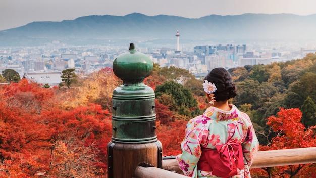 Donna asiatica che indossa bello kimono che cammina e che viaggia nel giardino giapponese dentro il tempio con le foglie di acero rosse in autunno. Foto Premium