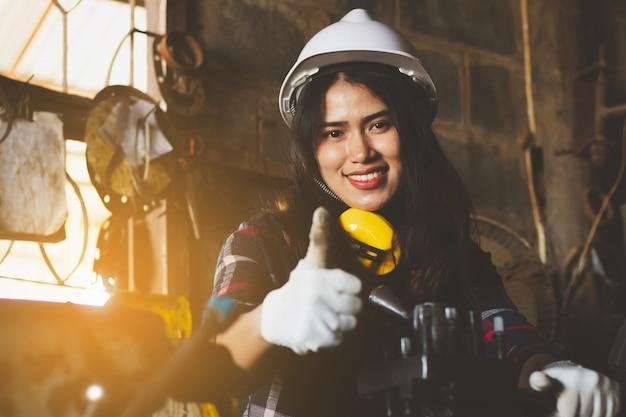 Donna asiatica che lavora in fabbrica, industria che utilizza macchina con felice. Foto Premium