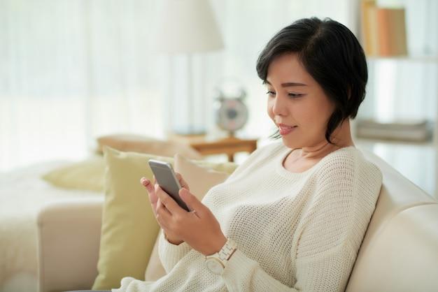 Donna asiatica che si rilassa a casa facendo uso dello smartphone Foto Gratuite
