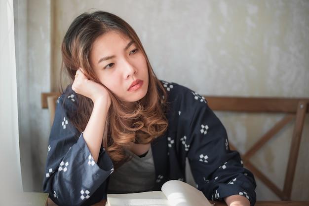 Donna asiatica che si siede da solo e depresso Foto Premium