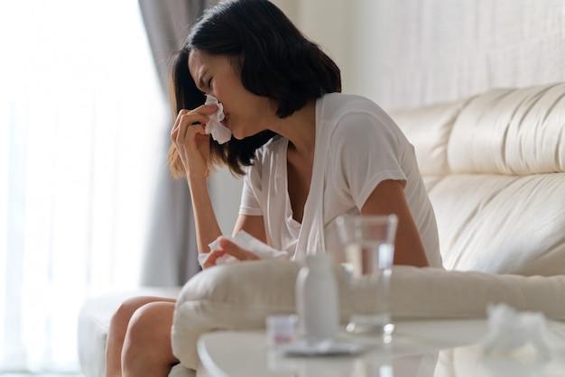Donna asiatica che si siede sul sofà a casa che ha una febbre fredda che usando tessuto per pulire il suo naso. Foto Premium