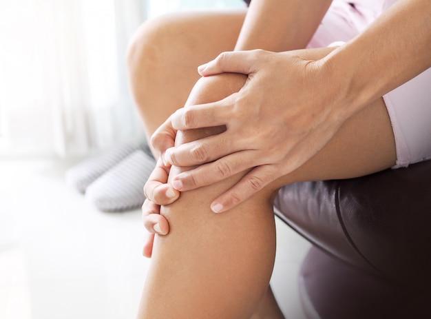 Donna asiatica che soffre di dolore alle gambe e al ginocchio. Foto Premium