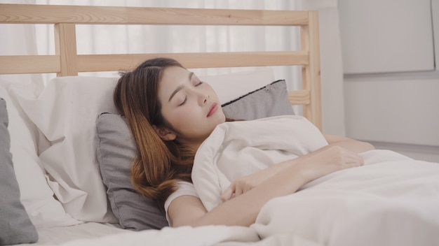 Donna asiatica che sogna mentre dormendo sul letto in camera da letto Foto Gratuite