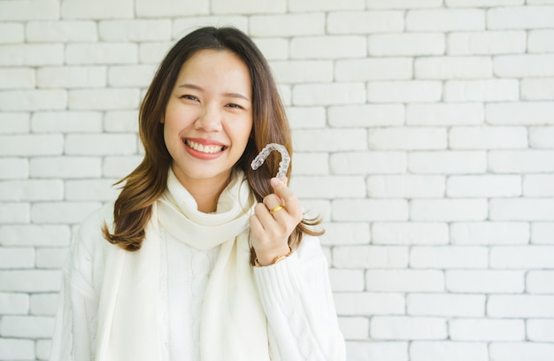 Donna asiatica che sorride con la mano che tiene fermo dentale aligner (invisibile) Foto Premium