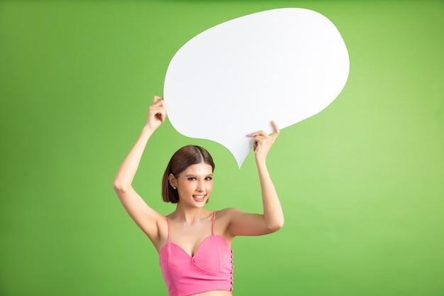 Donna asiatica che tiene e che rispetta al fumetto con spazio vuoto per testo su verde Foto Gratuite
