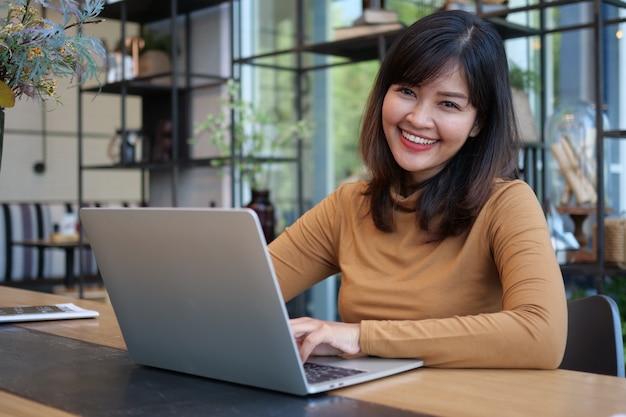 Donna asiatica che utilizza computer portatile nel caffè della caffetteria Foto Premium