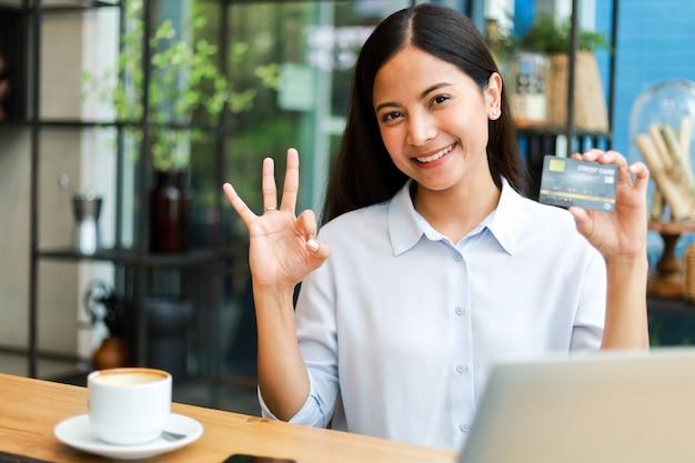 Donna asiatica che utilizza la carta di credito che compera online nel caffè della caffetteria Foto Premium