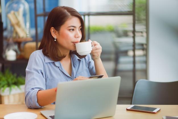 Donna asiatica che utilizza telefono cellulare con la carta di credito e il computer portatile per il pagamento online di compera nel caffè della caffetteria con gli amici Foto Premium