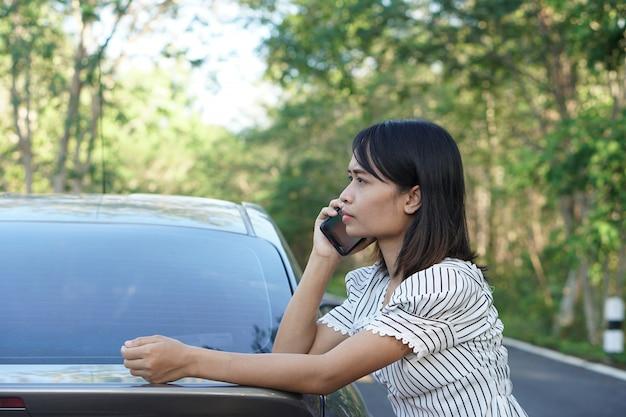 Donna asiatica chiama un meccanico, l'auto esce sulla strada intorno alla foresta. Foto Premium