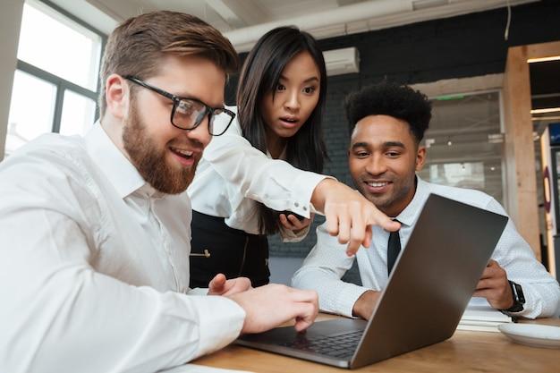 Donna asiatica colpita che mostra esposizione del computer portatile ai suoi colleghi Foto Gratuite