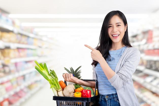 Donna asiatica con il cestino della spesa pieno delle drogherie in supermercato Foto Premium