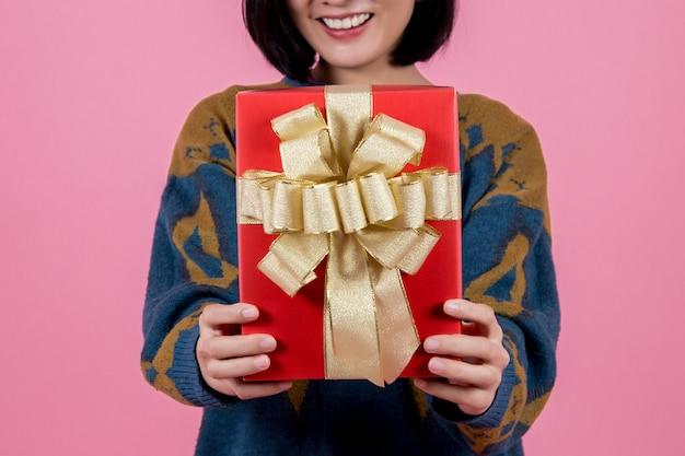 Donna asiatica con il regalo a backgrond rosa. Foto Premium