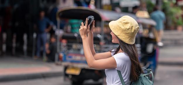 Donna asiatica del viaggiatore felice sul mercato di strada con la macchina fotografica, nella città di bangkok della tailandia. Foto Premium
