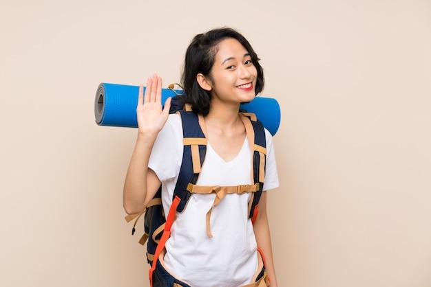 Donna asiatica del viaggiatore sopra fondo isolato che saluta con la mano con l'espressione felice Foto Premium
