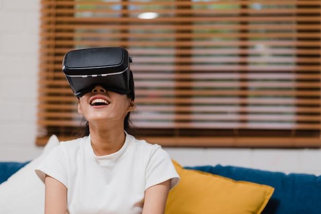 Donna asiatica dell'adolescente che utilizza il simulatore di realtà virtuale di vetro che gioca i video giochi in salone Foto Gratuite