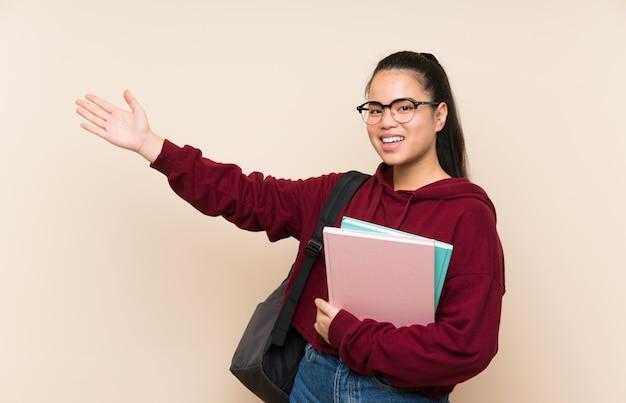 Donna asiatica della ragazza del giovane studente sopra le mani estendenti isolate della parete al lato per l'invito a venire Foto Premium