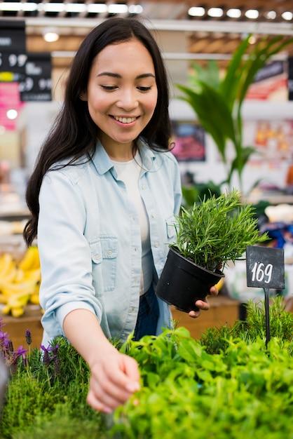 Donna asiatica felice che sceglie pianta in drogheria Foto Gratuite