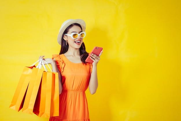 Donna asiatica felice che utilizza telefono cellulare su fondo giallo, stagione di autunno Foto Premium