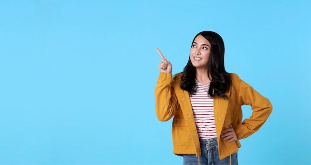 Donna asiatica felice sorridente con il suo indicare del dito isolata sul fondo blu-chiaro dell'insegna con lo spazio della copia. Foto Gratuite