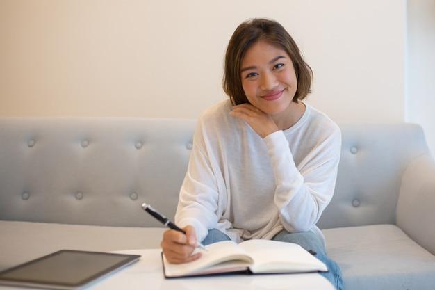 Donna asiatica graziosa sorridente che studia a casa Foto Gratuite