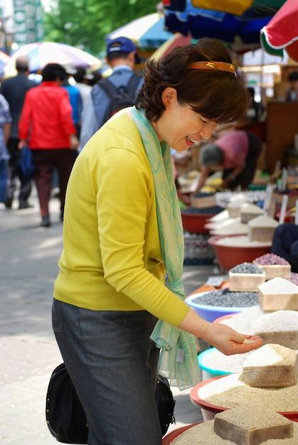 Donna asiatica guardando cereali nel mercato Foto Gratuite