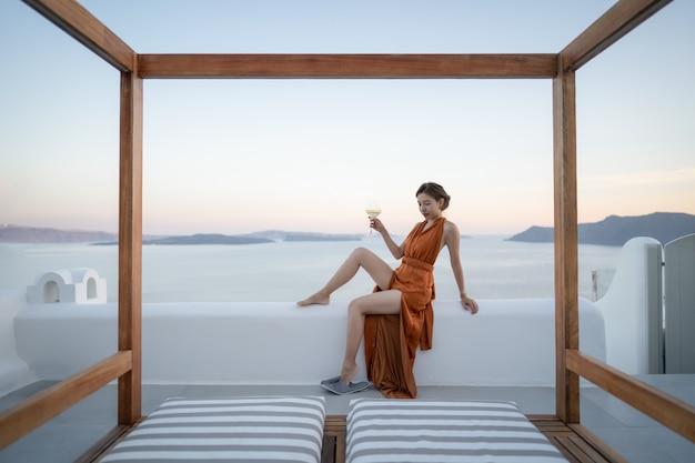 Donna asiatica in abito sexy con un bicchiere di vino godendo vista villaggio di oia nell'isola di santorini, in grecia. Foto Premium