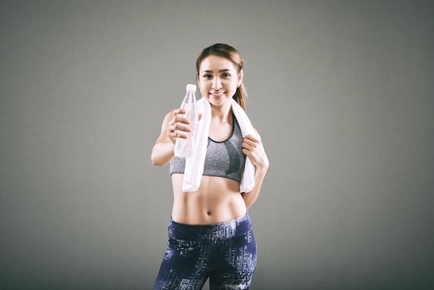 Donna asiatica in forma sorridente in abiti sportivi, con un asciugamano sulle spalle, tendendo una bottiglia d'acqua Foto Gratuite