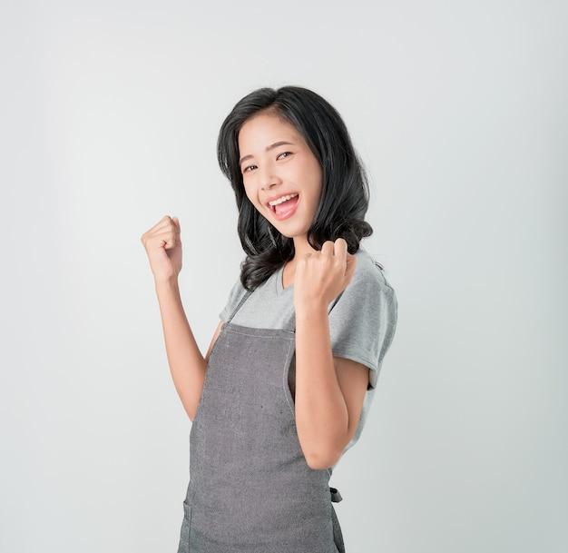 Donna asiatica in grembiule e in piedi con stupito per il successo e guardando avanti su sfondo grigio Foto Premium