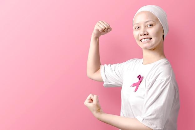 Donna asiatica in una camicia bianca con il nastro rosa sopra il rosa Foto Premium