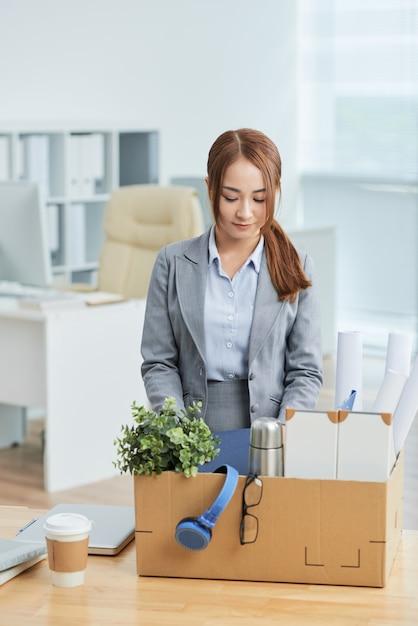 Donna asiatica in vestito che sta nell'ufficio con gli effetti personali in scatola di cartone sullo scrittorio Foto Gratuite