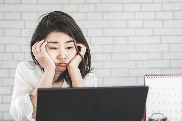 Donna asiatica insonne stanco e assonnato sul posto di lavoro Foto Premium