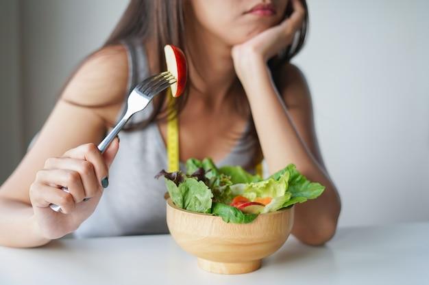 Donna asiatica noiosa da mangiare insalata o dieta alimentare. concetto di dieta Foto Premium